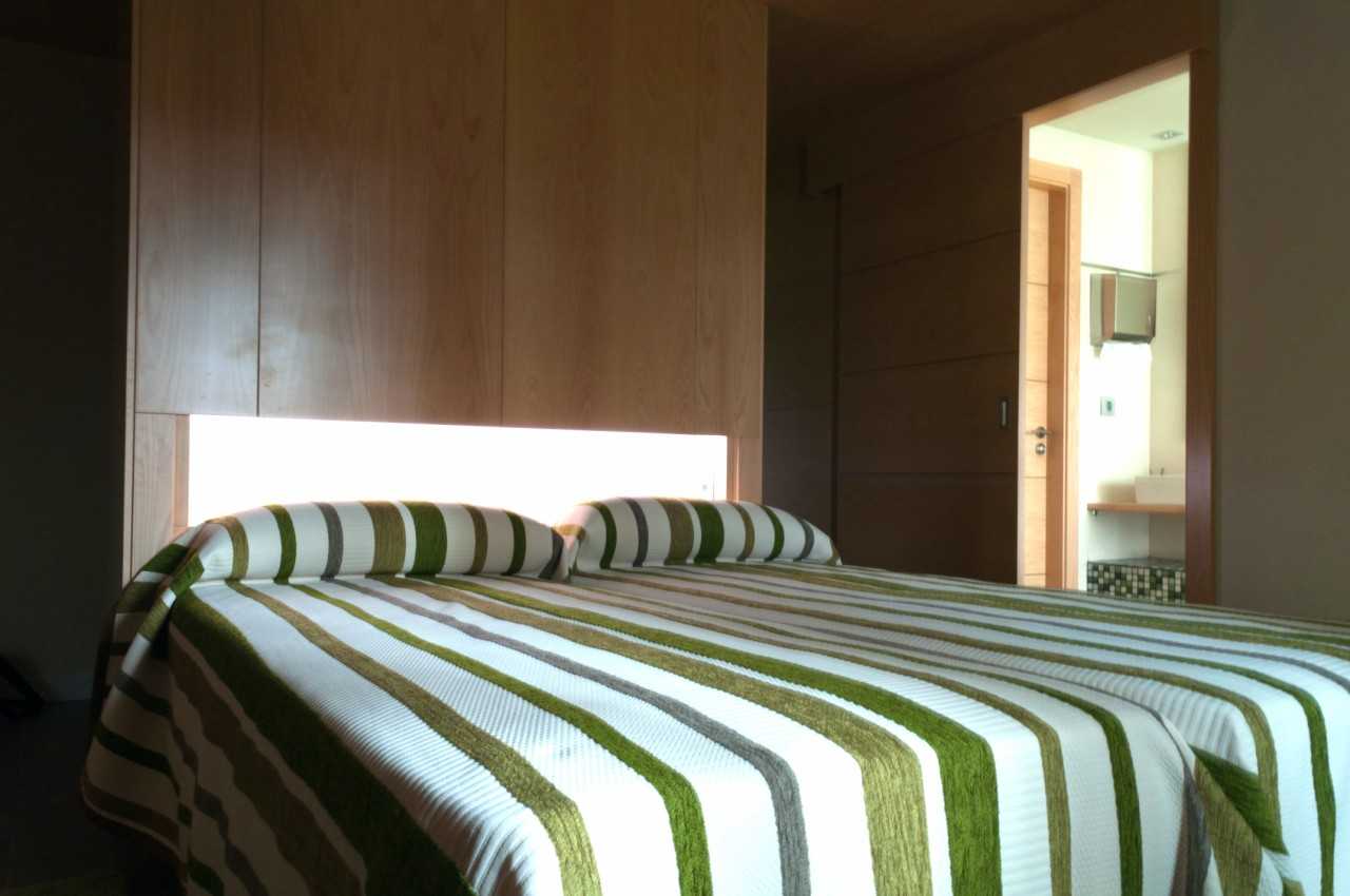 Habitación ambientada en color verde con 2 camas individuales, aseo con baño y ducha efecto lluvia.